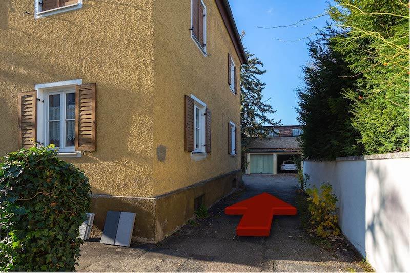 Ein Pfeil der den weiteren Weg, am Vorderhaus vorbei in den Innenhof und zur Osteopathiepraxis von Christian Kästle zeigt